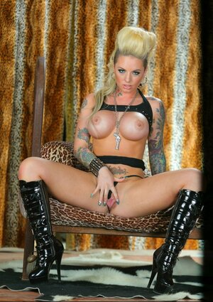 Alt blonde with huge breasts Christy Mack provocatively poses on sofa